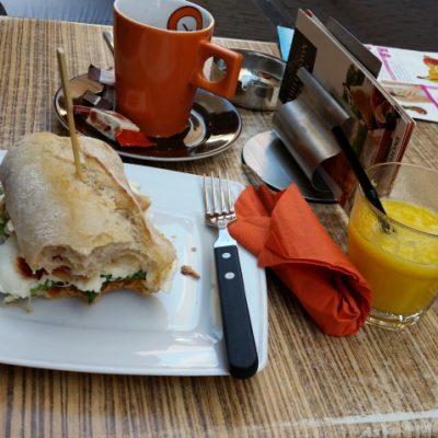 Обядът ми за 10 евро - сандвич със прошуто, песто и сушени домати, фреш от манго и портокал, дълго еспресо и минерална вода